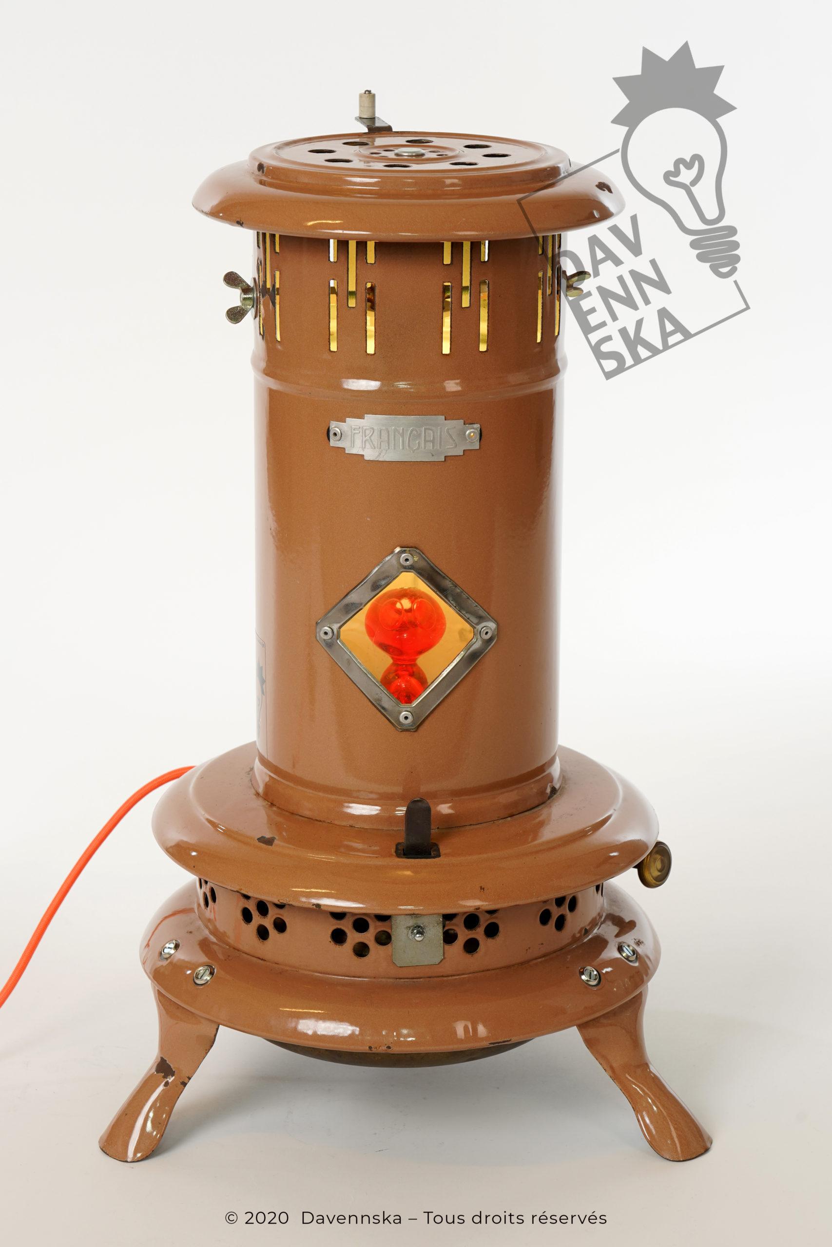 Un poêle à pétrole en tôle émaillée de couleur ocre de la marque Français, décoré d'un extra terrestre koziol orange et équipé d'une ampoule led multicolore